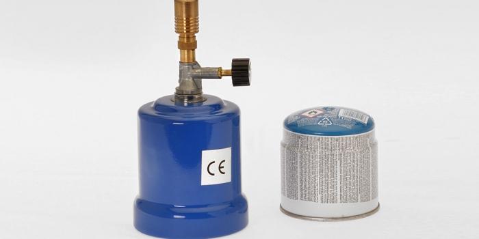 Metalowy PALNIK GAZOWY z nabitym kartuszem wyposażony dodatkowo w metalowy trójnóg, siatkę ceramiczną i zapasowy pojemnik gazowy (kartusz).